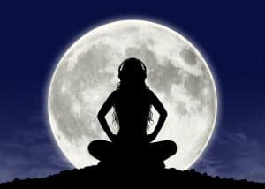 silhouette of a young beautiful woman with long hair in headphones in meditation posture with the full moon on the background